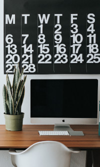 Computer desk with calendar above it